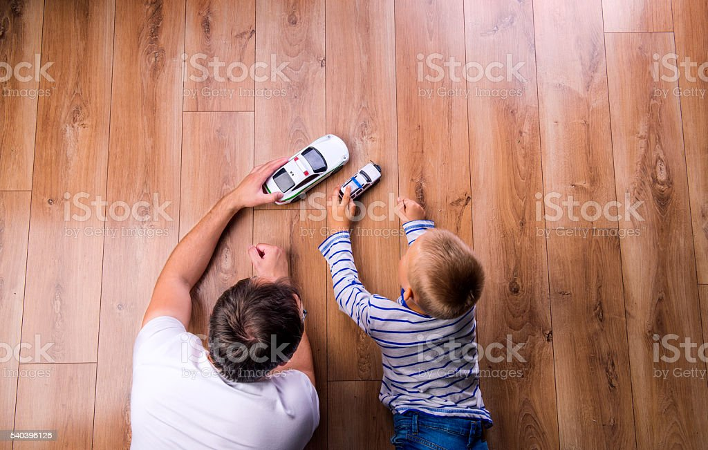 Unrecognizable father with his son playing with cars stock photo