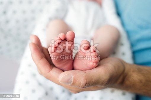 Unrecognizable father with newborn baby son, legs and hand. Close up.