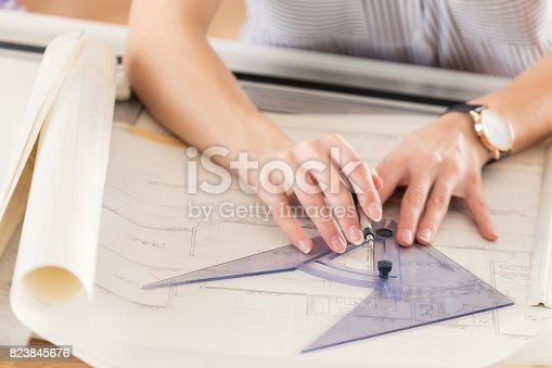 476601452 istock photo Unrecognizable female architect draws blueprint with protractor 823845676