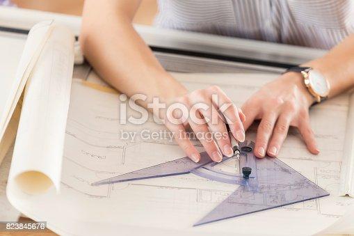 istock Unrecognizable female architect draws blueprint with protractor 823845676