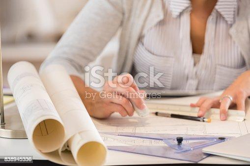 istock Unrecognizable female architect erases error on blueprint 838945336