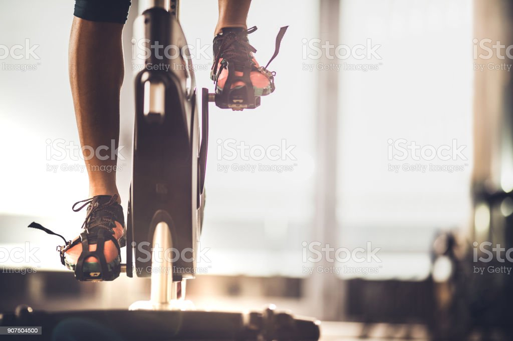 Unrecognizable female athlete exercising on exercise bike in a gym. stock photo