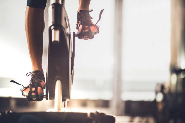 Unrecognizable female athlete exercising on exercise bike in a gym. Unrecognizable athletic legs during exercising training in a health club. exercise bike stock pictures, royalty-free photos & images