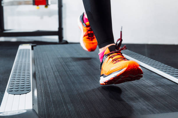 Unrecognizable female athlete running on a treadmill Close up of a person jogging on a treadmill in fitness center. Warming up with some cardio training. training equipment stock pictures, royalty-free photos & images