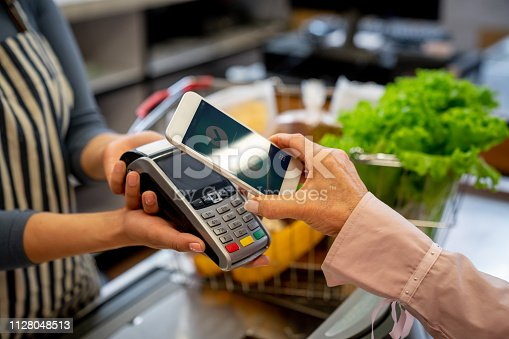 Unrecognizable female customer paying for groceries with smartphone **DESIGN ON SCREEN WAS MADE FROM SCRATCH BY US**