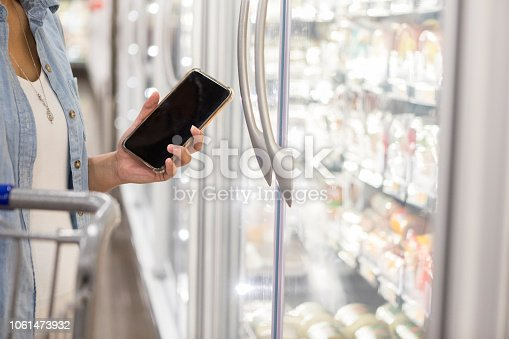istock Unrecognizable female holds her smartphone to compare prices at supermarket 1061473932