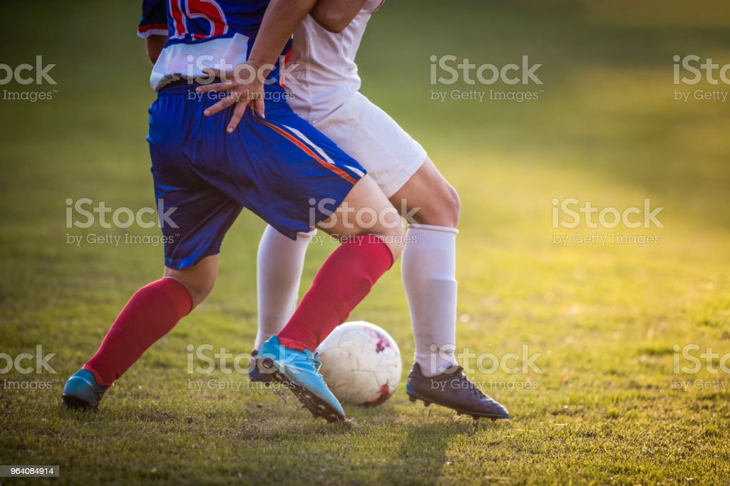 Unrecognizable female soccer player keeping the ball safe from her rival on a match. - Royalty-free Adolescence Stock Photo