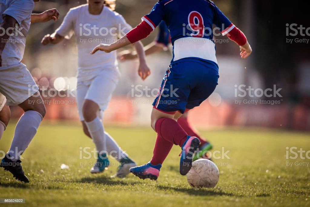 Unrecognizable female soccer players tackling on playing field. stock photo