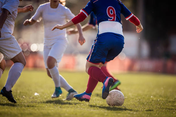 unrecognizable female soccer players tackling on playing field. - soccer competition stock photos and pictures
