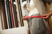 Unrecognizable female trying out a red leather belt in a bags and accessories store