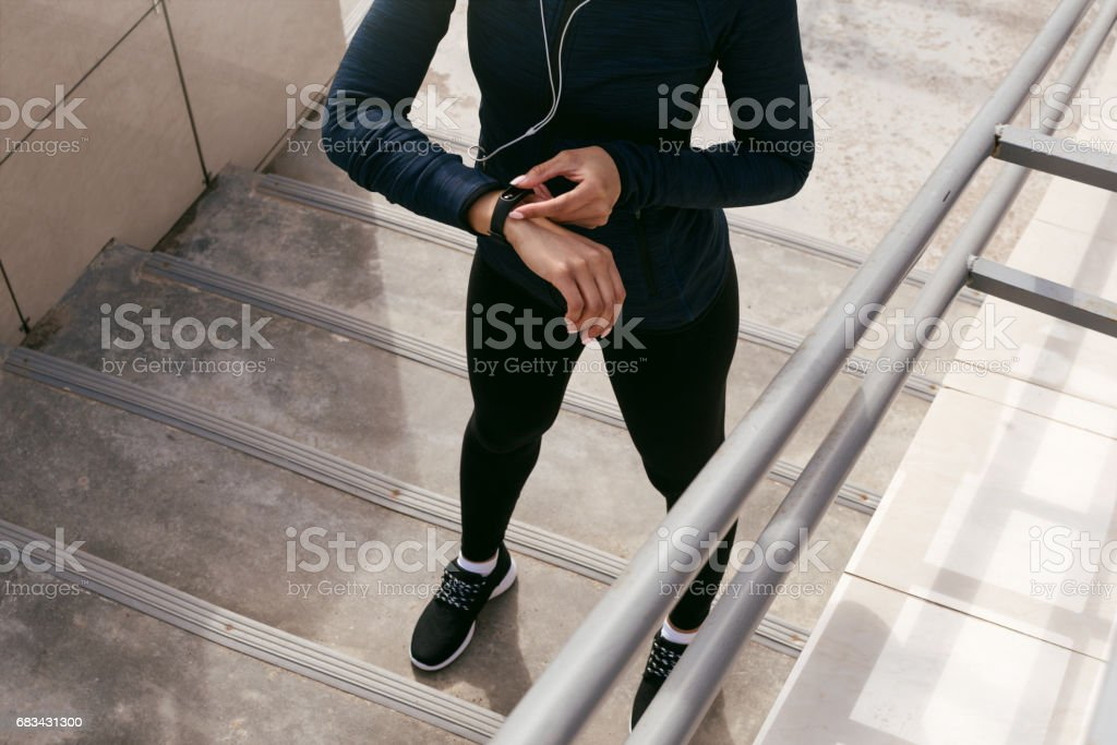 Unrecognizable female using fitness tracker after training stock photo