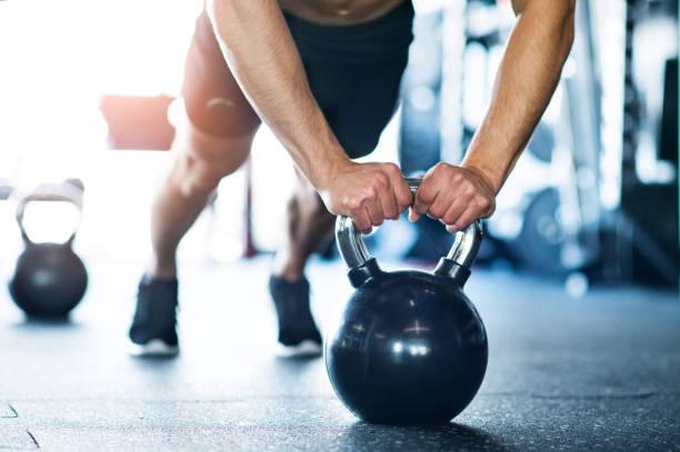 unkenntlich fit mann im fitnessraum tun push ups auf kettlebells - konzentrationsübungen stock-fotos und bilder