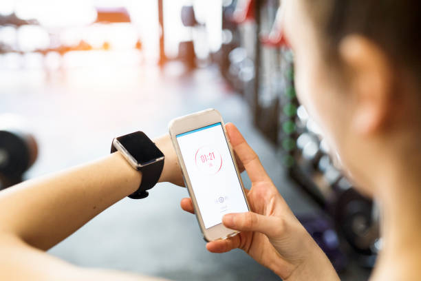 Unrecognizable fit woman in gym with smart phone and smart watch. stock photo