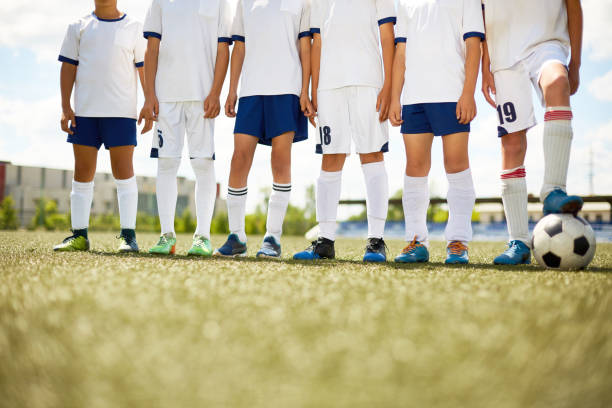 unrecognizable football team in field - soccer competition stock photos and pictures