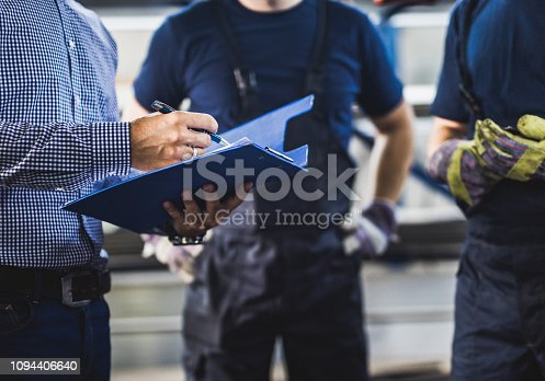 istock Unrecognizable foreman going through paperwork with manual workers in a warehouse. 1094406640