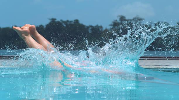 close-up: garota irreconhecível mergulha cristalina piscina em dia quente de verão. - mergulho - fotografias e filmes do acervo