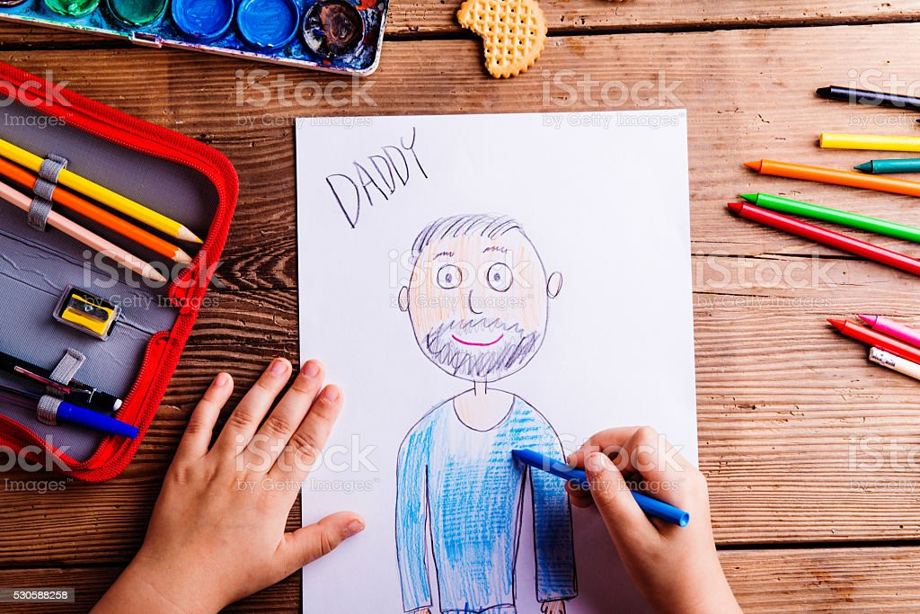 Unrecognizable girl drawing picture of her father. Wooden backgr stock photo