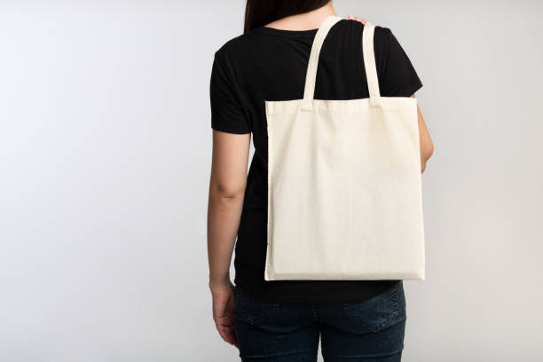 unrecognizable girl holding eco bag on white background, back view - tote bag imagens e fotografias de stock
