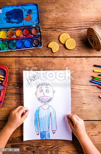 istock Unrecognizable girl holding picture of her father. Wooden backgr 537381358
