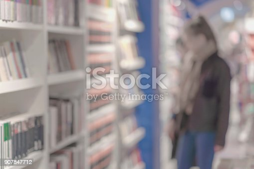 istock Unrecognizable Girl in bookstore. Many of interesting books. Education, school, study, reading fiction concept. Light background 907847712