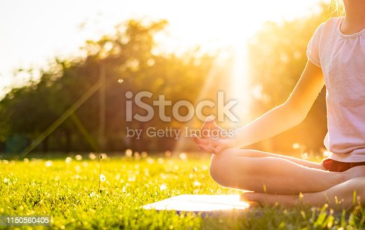 Unrecognizable girl meditate sitting on grass at sunset