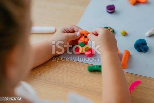 An anonymous little girl playing with plasticine.
