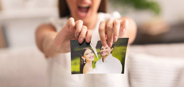 Unrecognizable Girl Tearing Apart Photo Of Happy Couple Indoor, Cropped Divorce Concept. Unrecognizable Furious Girl Tearing Apart Photo Of Happy Couple Indoor. Selective Focus, Panorama, Cropped former stock pictures, royalty-free photos & images