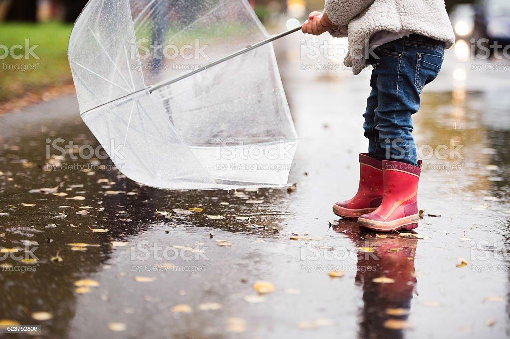 Unrecognizable girl with transparent umbrella on rainy day. stock photo