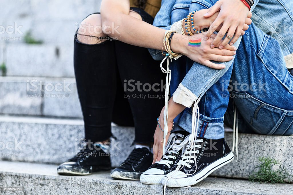 Unrecognizable girls embracing and sitting on stairs stock photo