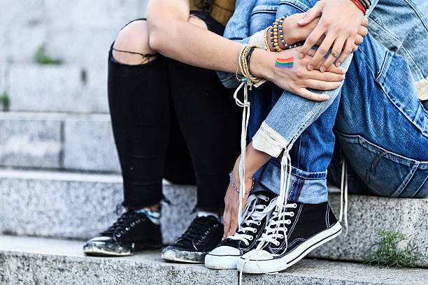 Unrecognizable girls embracing and sitting on stairs Two young girls holding hands, embracing and sitting on stairs. One with rainbow flag on hand. Both with casual clothes. Focus on foreground. transgender stock pictures, royalty-free photos & images