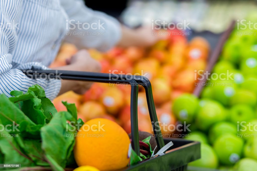 Unrecognizable grocery store customer reaches for fresh produce stock photo