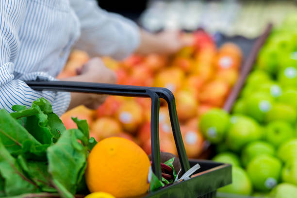 Unrecognizable grocery store customer reaches for fresh produce Unrecognizable female supermarket customer reaches for fresh oranges while shopping for produce. Focus is on a shopping basket filled with leafy greens and fresh oranges. produce aisle stock pictures, royalty-free photos & images