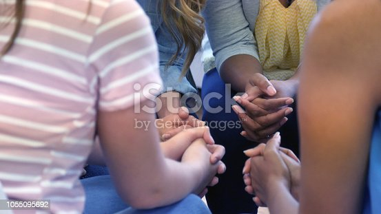 1055095320 istock photo Unrecognizable group of women pray in a circle 1055095692