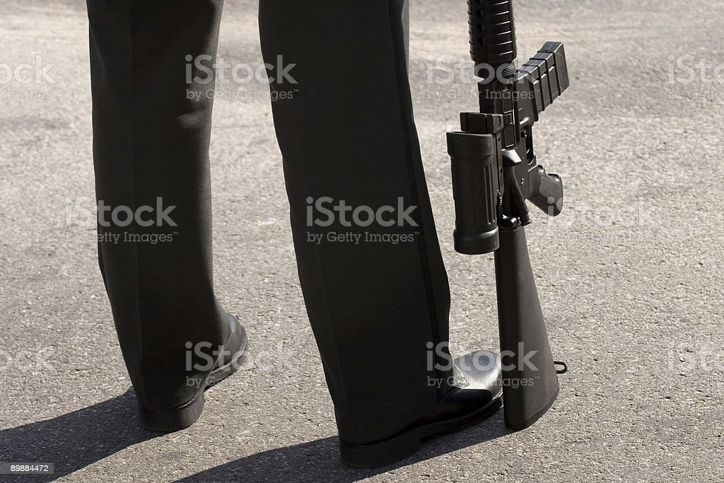 unrecognizable guard with his gun resting on the ground royalty-free stock photo