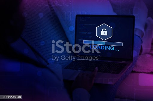 Cybercrime Concept. Unrecognizable hacker using laptop with progress loading bar on screen in dark room, view over shoulder