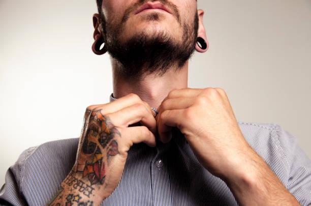 nicht erkennbare hipster mann polstertechniken shirt - gedehnte ohren stock-fotos und bilder