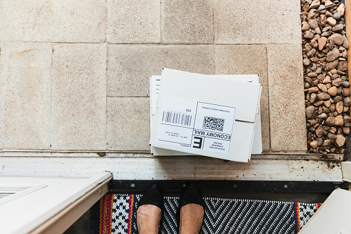 The unrecognizable female homeowner looks down at the mail left on her doorstep.