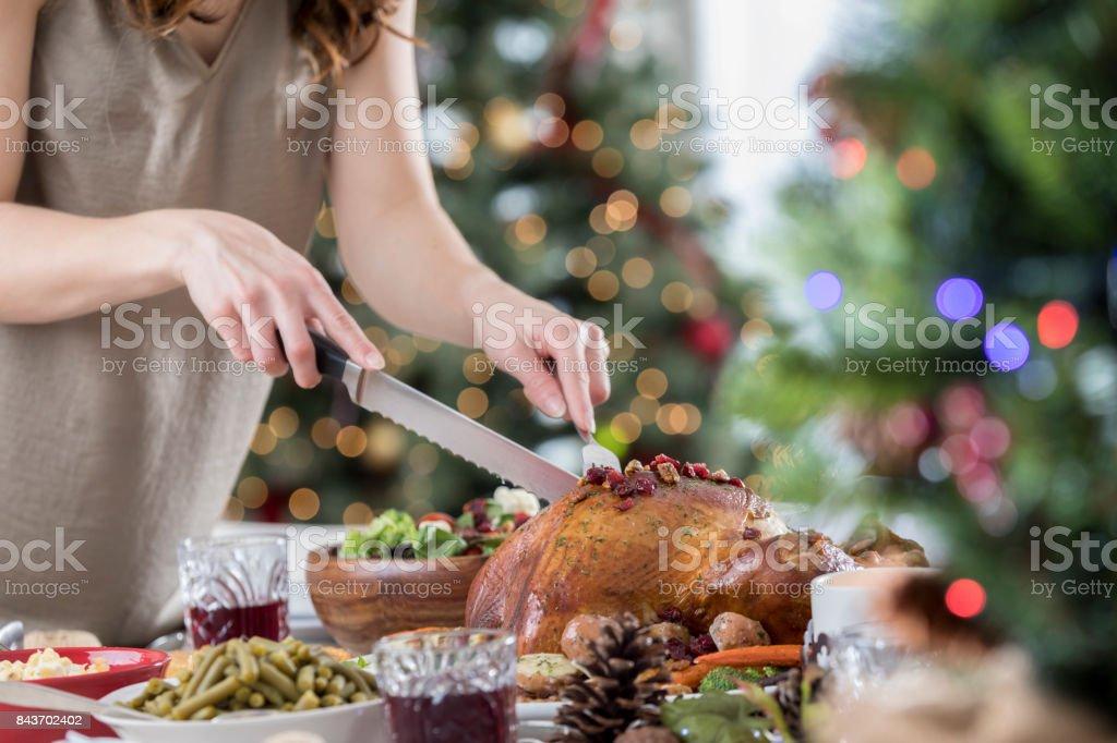 Unrecognizable hostess carves Christmas turkey before dinner stock photo