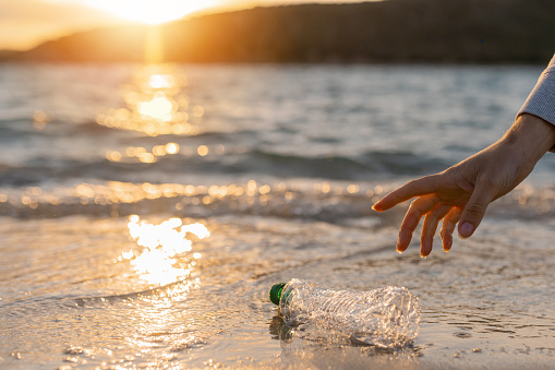 Unrecognizable human hand picking up a plastic bottle waste on the beach shore with beautiful sunset on the sea on background.