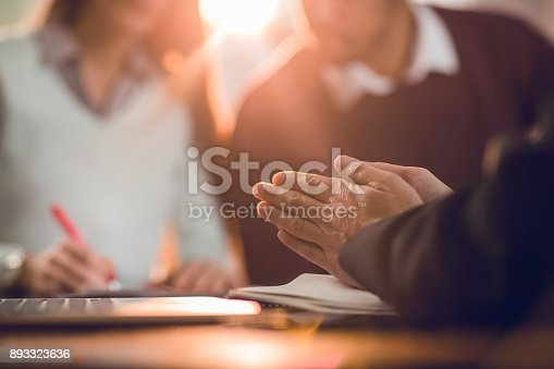 istock Unrecognizable insurance agent rubbing his hands while making a fraud. 893323636
