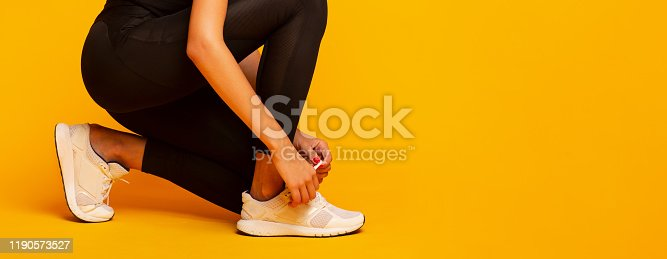 Unrecognizable Lady Lacing Shoes Before Fitness Workout Over Yellow Background In Studio. Cropped, Panorama, Empty Space