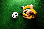 istock Unrecognizable little football player against green grass, studi 538778016