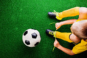 istock Unrecognizable little football player against green grass, studi 544809756