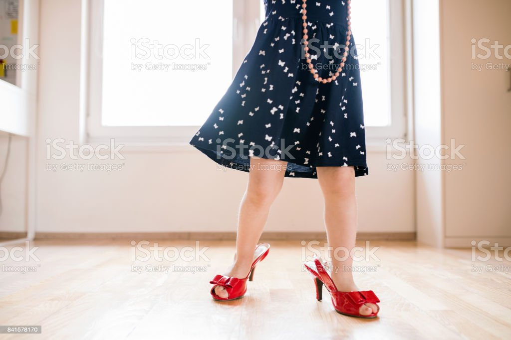 Unrecognizable little girl in dress and red high heels at home. stock photo