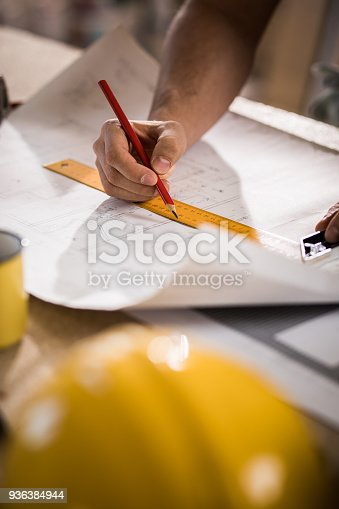 istock Unrecognizable male architect making measurements and drawing on housing project. 936384944