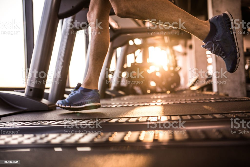Unrecognizable male athlete running on treadmill in health club. stock photo