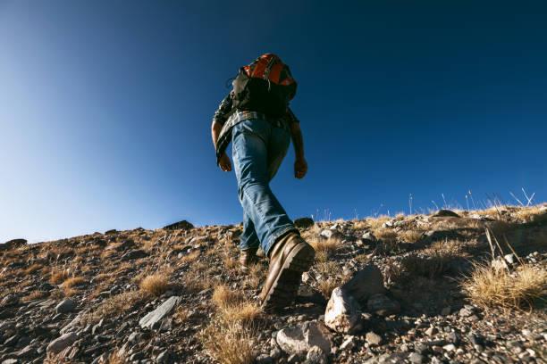 Unrecognizable male traveler goes uphill