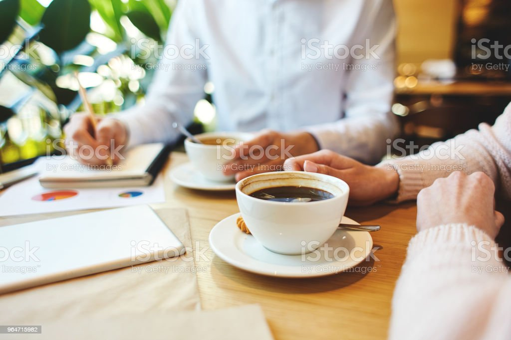 Unrecognizable man and woman sitting with coffee cups at cafe table, discussing business and taking down notes in pad. royalty-free stock photo