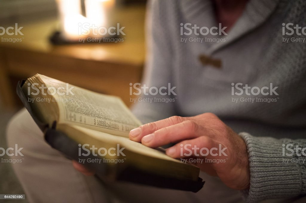 Unrecognizable man at home reading Bible, burning candles behind him - foto stock