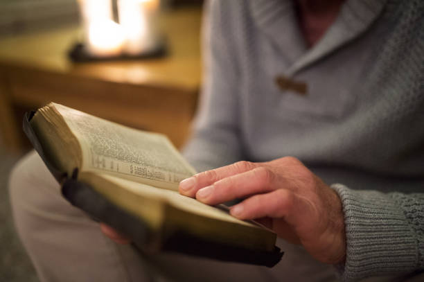 Unrecognizable man at home reading Bible, burning candles behind him stock photo
